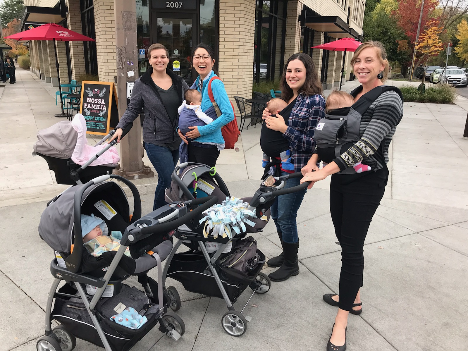 Four ladies with strollers and infants in front of a coffee shop