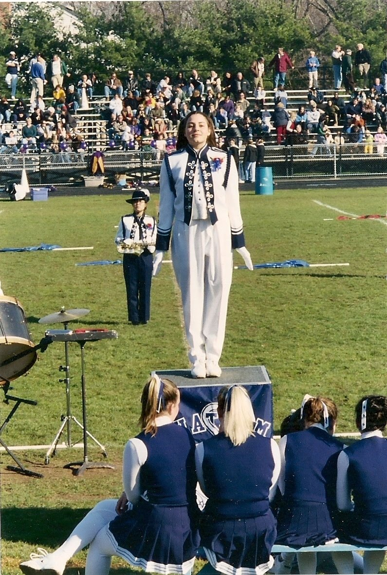 high school female in white and blue marching band attire, standing on a podium in front of a field, with an audience in the stands in the background, cheerleaders sitting on a bench in the foreground
