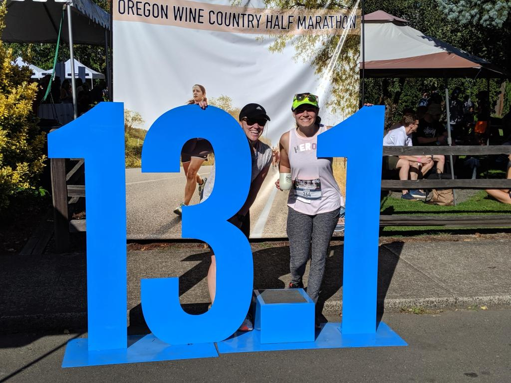 "two women standing by a giant 13.1 statue, in front of a sign saying ""Oregon Wine Country Half Marathon"""