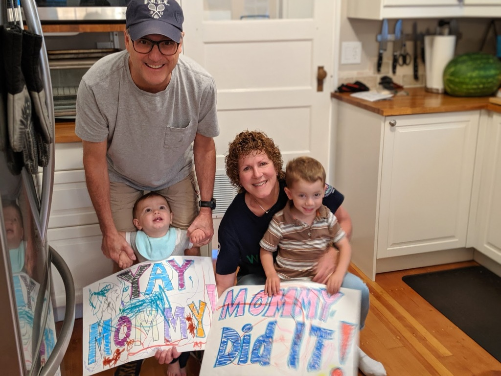 "kids and grandparents holding hand-made signs saying ""yay mommy"" and ""mommy did it!"""